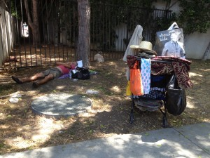 A homeless person with a cart full of belongings sleeping on WeHo's Eastside (Photo courtesy of Roxanne McBryde).